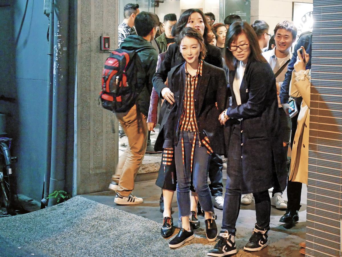 離開慶功宴,周冬雨(左)一身輕便,還要人護送她才走得出來,表情十分逗趣。