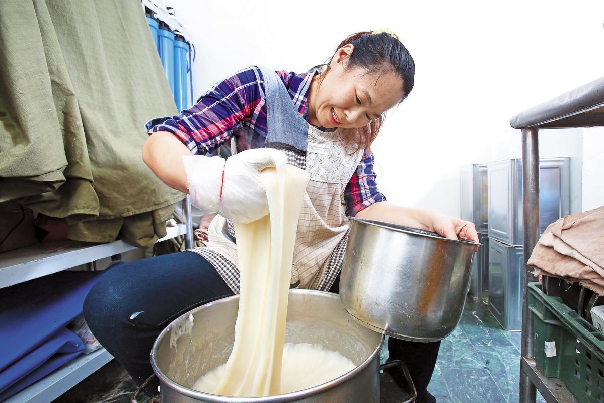 阿綿顧不得燙手,蒸好的麻糬高溫達150度,得趁軟糯時,快速分裝。