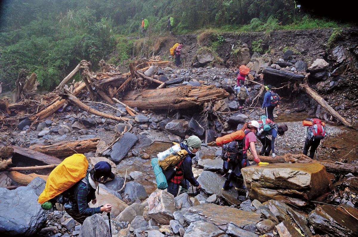 全無登山經驗的文大隊員面對崎嶇陡峭的溪谷必須手腳並用,加上不少枯木擋住山路,造成時程嚴重落後,比原訂時間晚了近5小時才抵達加羅湖。(文大推廣部職員提供)