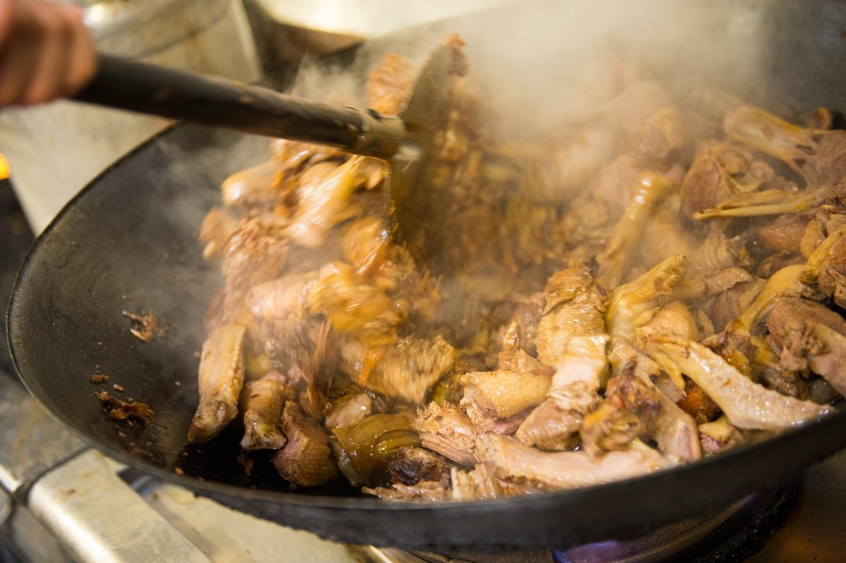 料理「薑母鴨」第一道程序,先以黑麻油煸香老薑,倒入鴨肉塊,加入白芍、當歸、肉桂等研磨的中藥粉翻炒到鴨肉約2分熟。