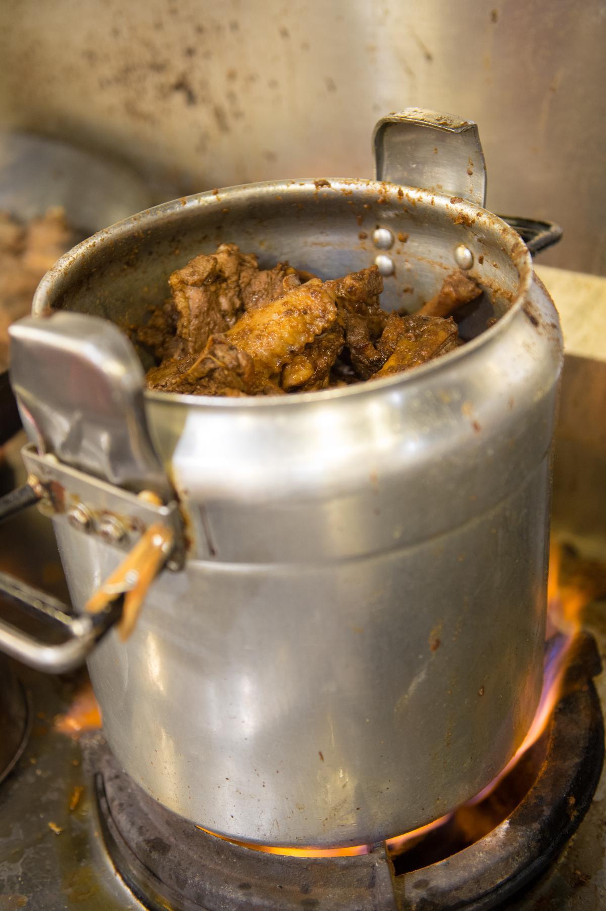 第二道程序是加入中藥粉炒香後的鴨肉,移入快鍋燜煮5至10分鐘,才能盛入陶鍋準備出場。