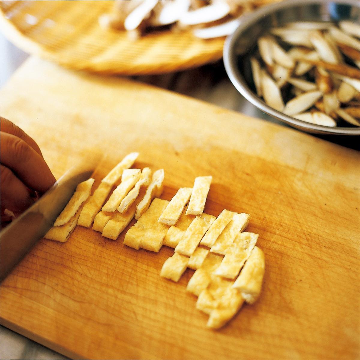 油豆腐皮對半切開,再切成1公分寬的長條。