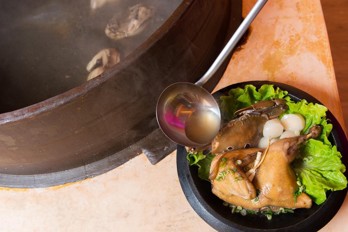用超大鑄鐵鍋熬煮「金蔘燉雞湯底」,湯頭甘美鮮甜。(490元/份,螃蟹、干貝得各加價150元)