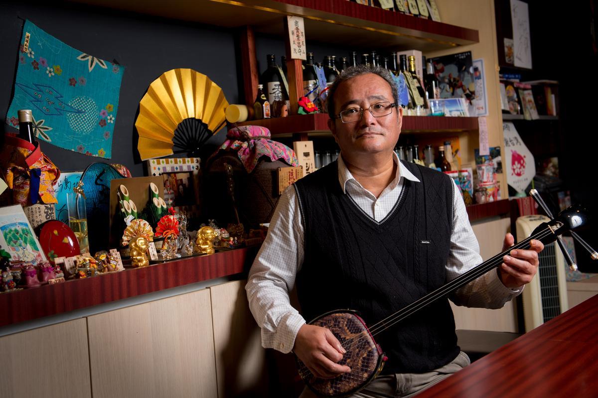 「美ら島」老闆諸喜田伸來台30多年,經常在店內拿起三味線自彈自唱。