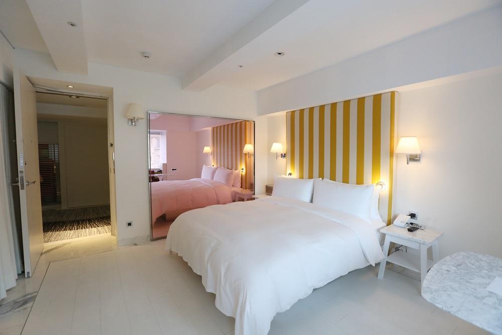 客房內也維持純白調性,大面積粉色鏡面牆增加空間感。