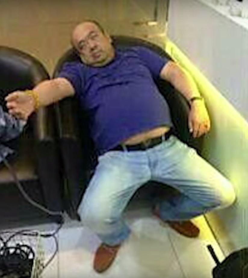 中毒的金正男生前最後影像,痛苦癱坐在機場椅子上。(翻攝StraitsTimes 網站)