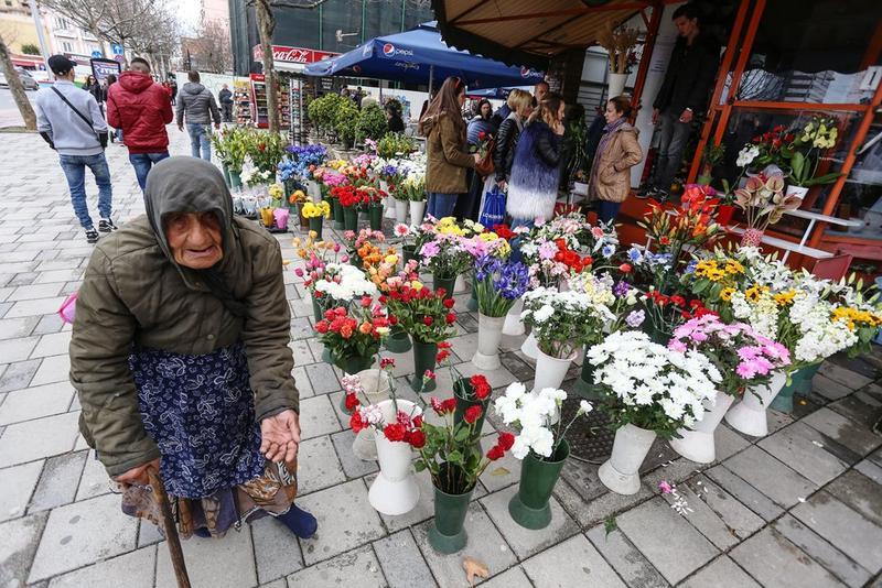 阿爾巴尼亞一名老婦人在花店前行乞。