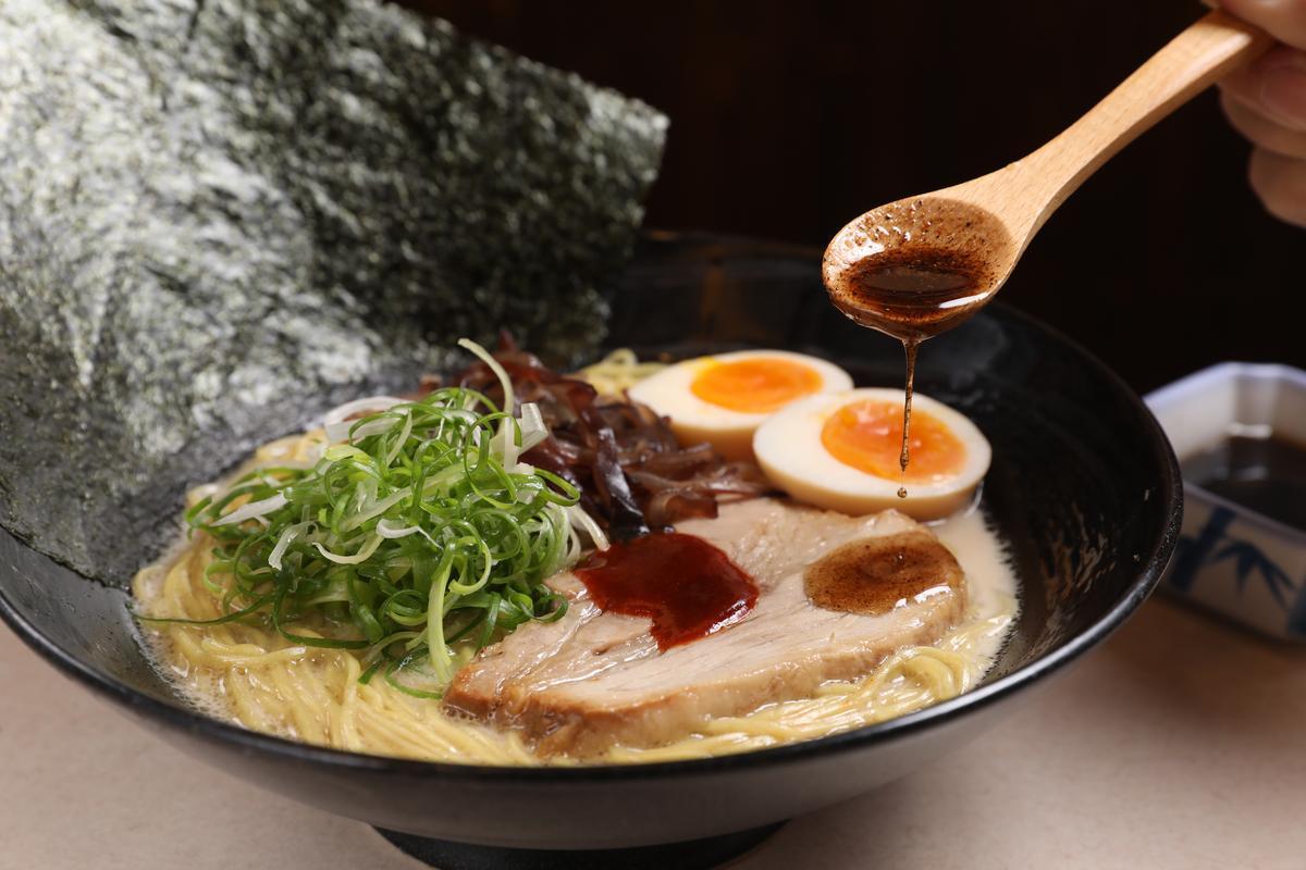 「黑九州細麵」會加進特製黑蒜油,作法是將炸到不同焦度的蒜頭混在一起,增添香氣層次。(270元/碗)