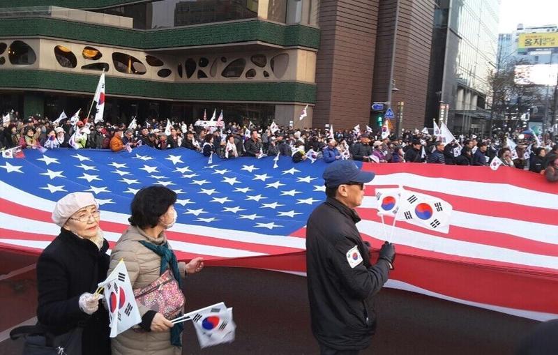 在首爾市廳廣場上,親朴派群眾一起拿著美國國旗,要求重視安保與支持部署薩德,主張彈劾總統全是陰謀。
