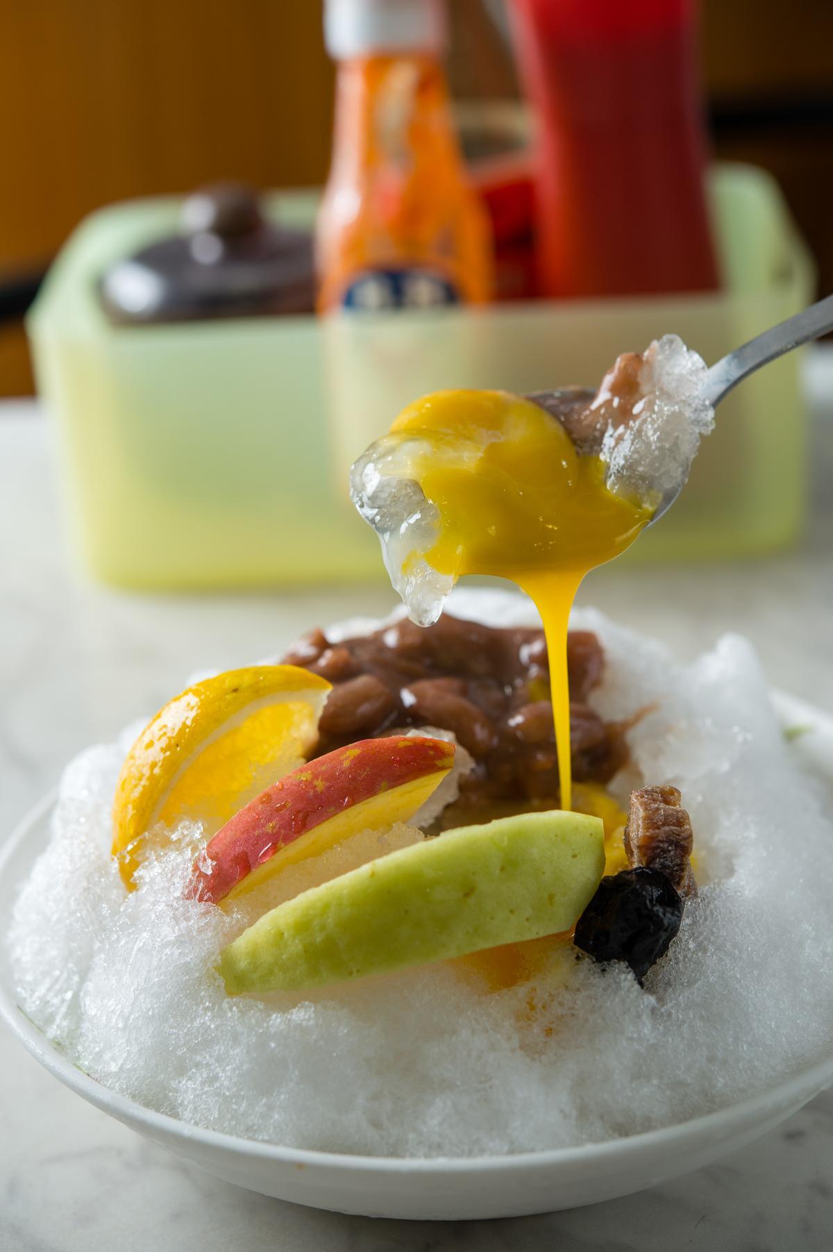 這一盤「花豆雞蛋刨冰」是創店43年來的功臣「老冰」,蜜餞、水果及濃稠花豆醬再加一顆生蛋黃,黃金組合譜出酸鹹鮮甜的滋味,在60 ~70年代常見經典款剉冰。(65元/份)