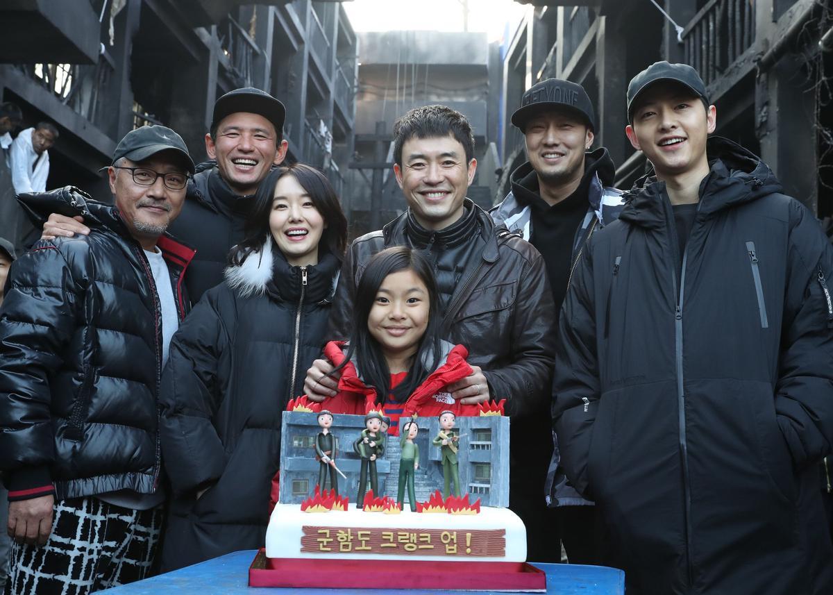 《軍艦島》殺青,導演與演員群一起切蛋糕慶祝。(左起金義聖、黃正民、李貞賢、金秀安、柳承莞、蘇志燮與宋仲基)網路圖片
