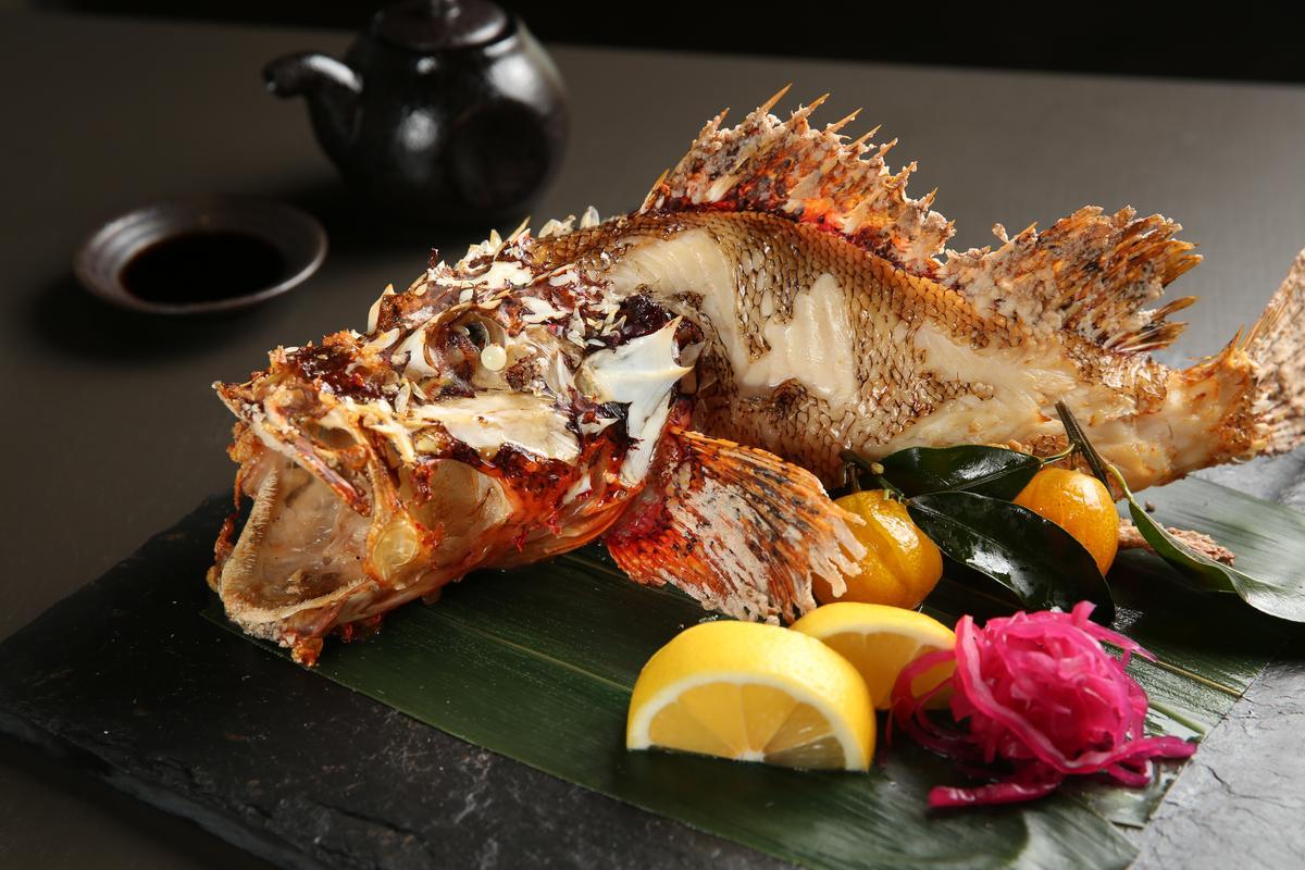 「鹽烤石狗公」採用立烤的方式呈現生動感,因肉質富有彈性,爐烤時魚皮會脹裂。(時價,圖中約980元)