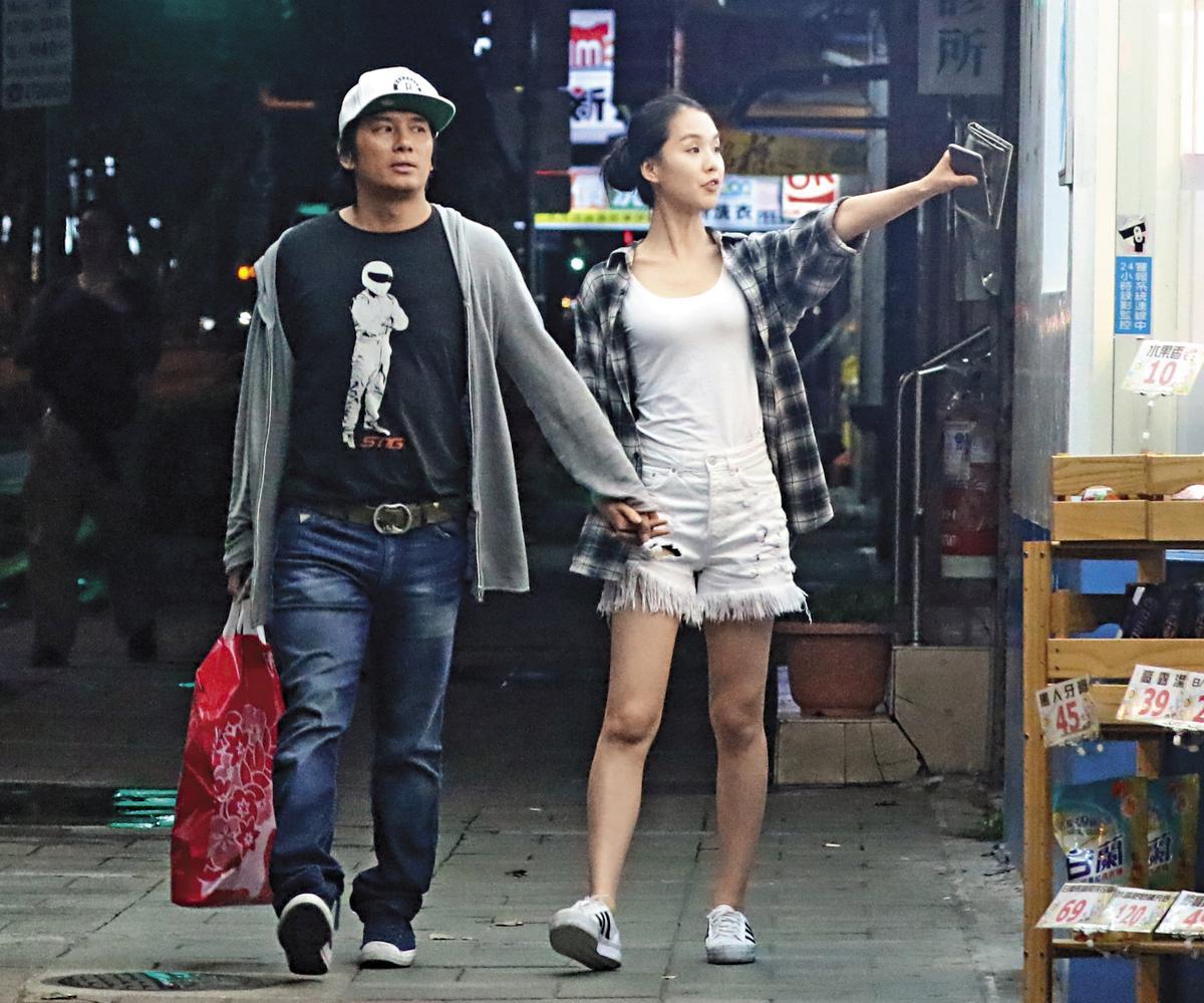 兩人步出賣場後,手牽手在馬路上逛大街。