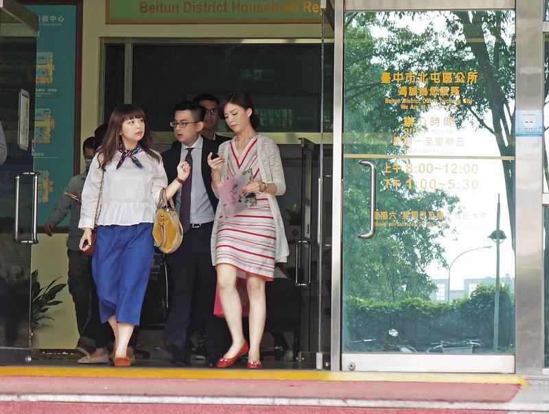 洪慈庸和卓冠廷24日在戶政事務所完成結婚登記,當天她盤著頭髮,穿著一襲白色套裝和紅色平底鞋,露出白皙修長美腿。讀者提供