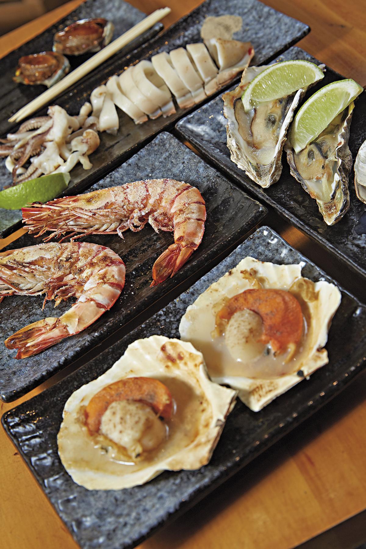 兩人份的「海鮮套餐」(799元),含軟絲、大蝦、生蠔、鮑魚、扇貝、海王螺、大蛤,分量十足。(原木燒烤海鮮)
