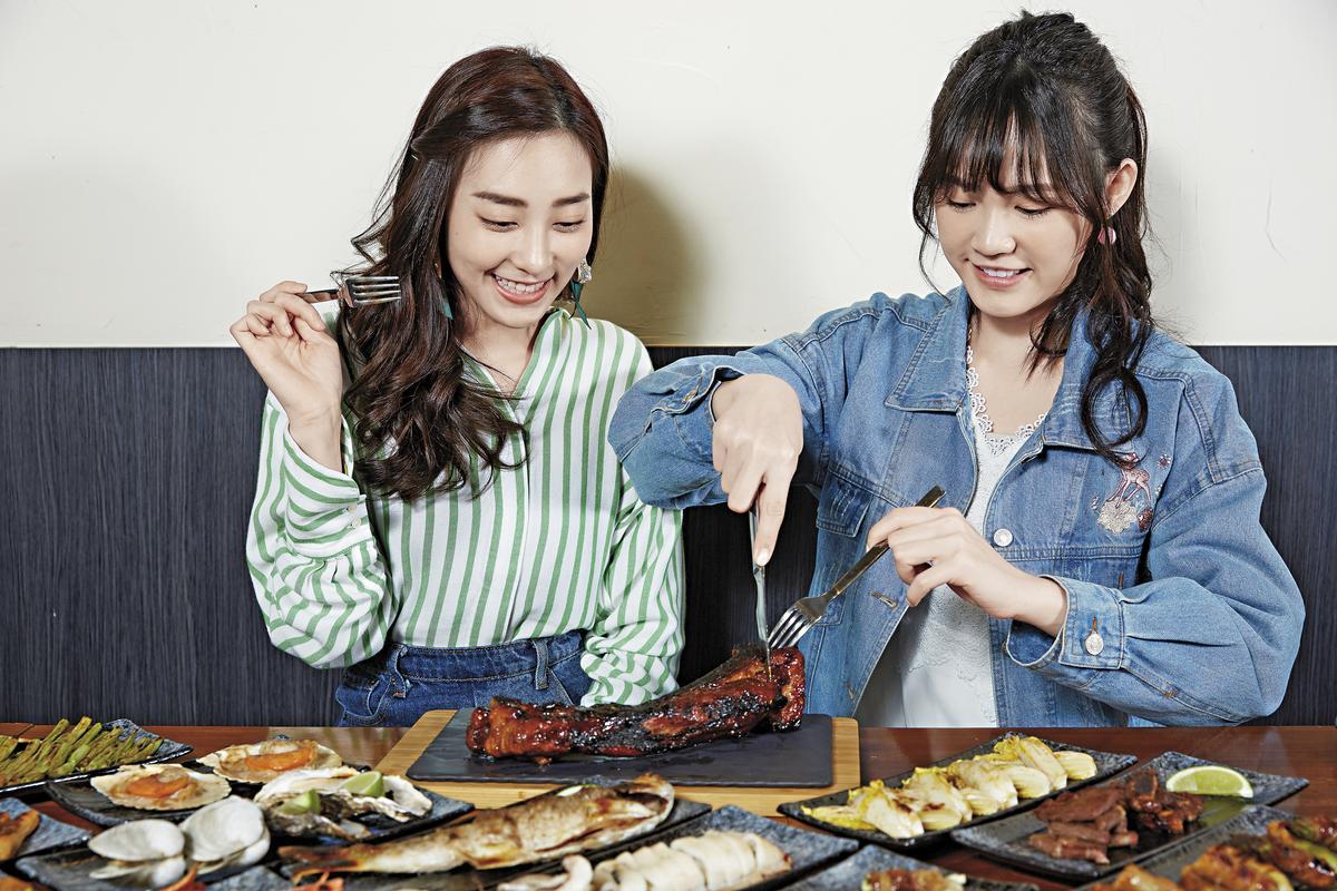 店家招牌「豬腩排」(350元),看吳心緹(右)切下豬腩排厚厚的肉層,肉汁緩緩流出。(原木燒烤海鮮)