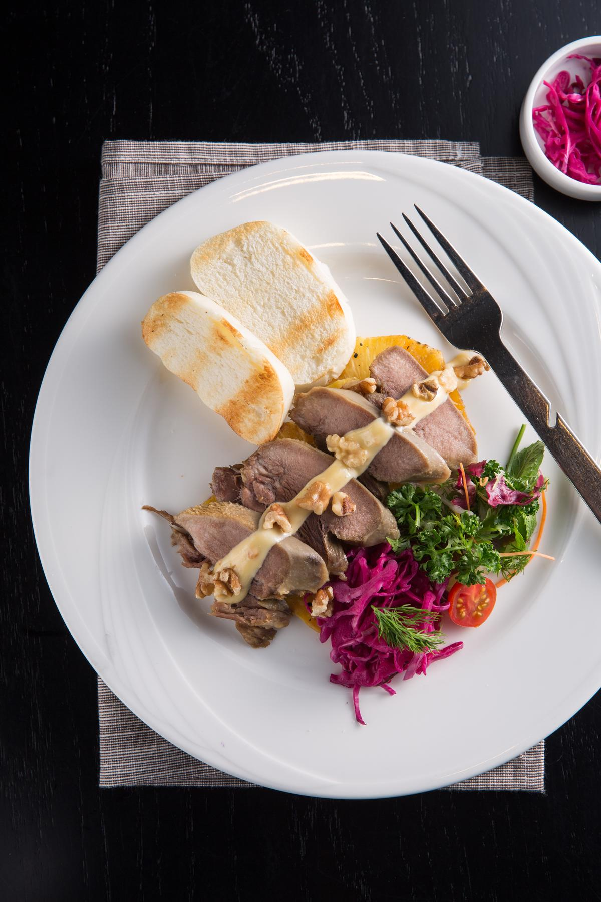 「鳳梨豆醬燉豬舌佐蘋果酸菜配烤饅頭」的豬舌彈牙爽脆,搭配紫色高麗菜酸菜,趣味組合讓人還想再吃一口。(450元/份)
