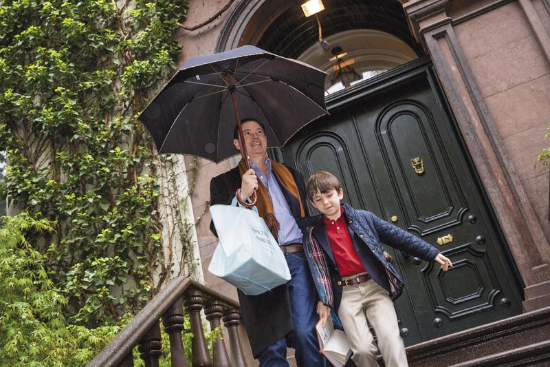 清早下起了大雨,約翰早已把車停妥在門外等候,安德魯(左)撐著傘護著喬治(右),兩夫夫正準備送孩子上學去。