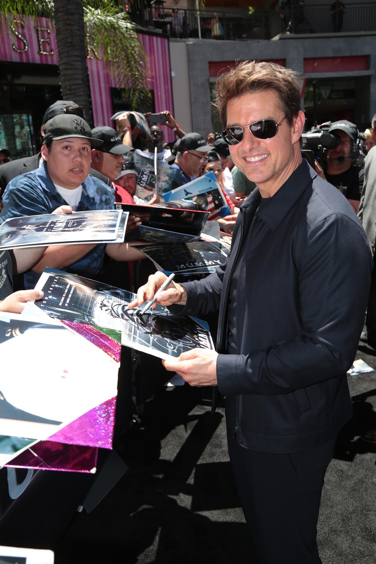 湯姆克魯斯替旁觀活動的民眾簽名。