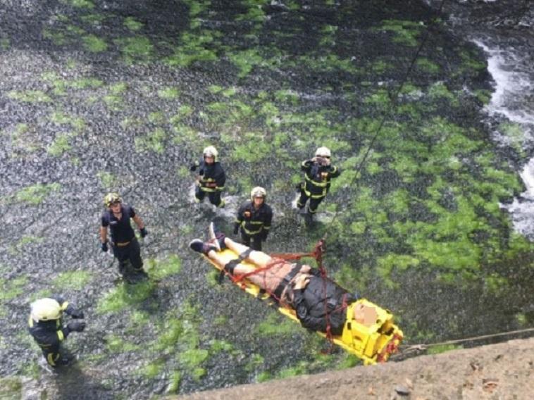 消防局以吊臂系統將死者的遺體吊掛上岸。