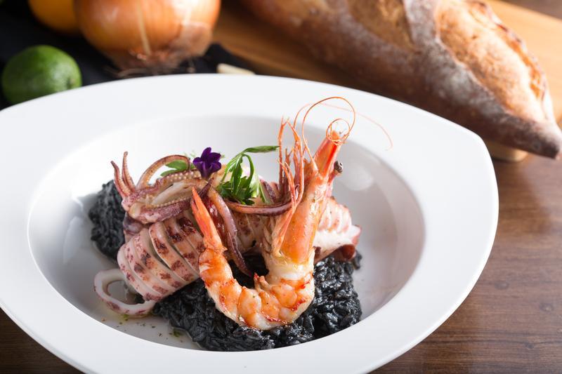 使用花蓮芋香米做成的「澎湖海鮮墨魚燉飯」,飽滿綿潤,還有一整隻彈嫰的澎湖小卷,海味鮮甜。(388元/份)