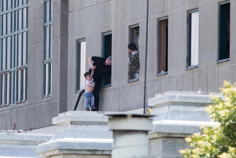 伊朗國會大樓發生恐怖攻擊,伊朗警方協助受困民眾與兒童撤離。(東方IC)