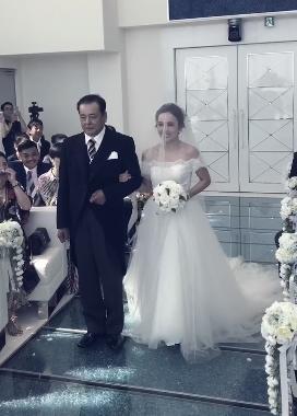 愛紗穿著絕美白紗、挽著父親的手步入禮堂。