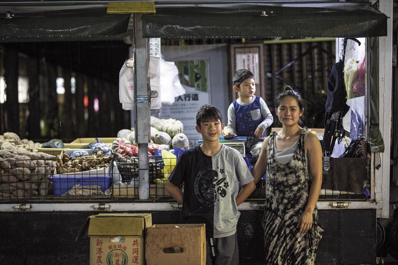 開著3噸半卡車南來北往,李沂(右)帶著2個兒子在西湖市場擺攤賣從中部批貨的地瓜、南瓜。