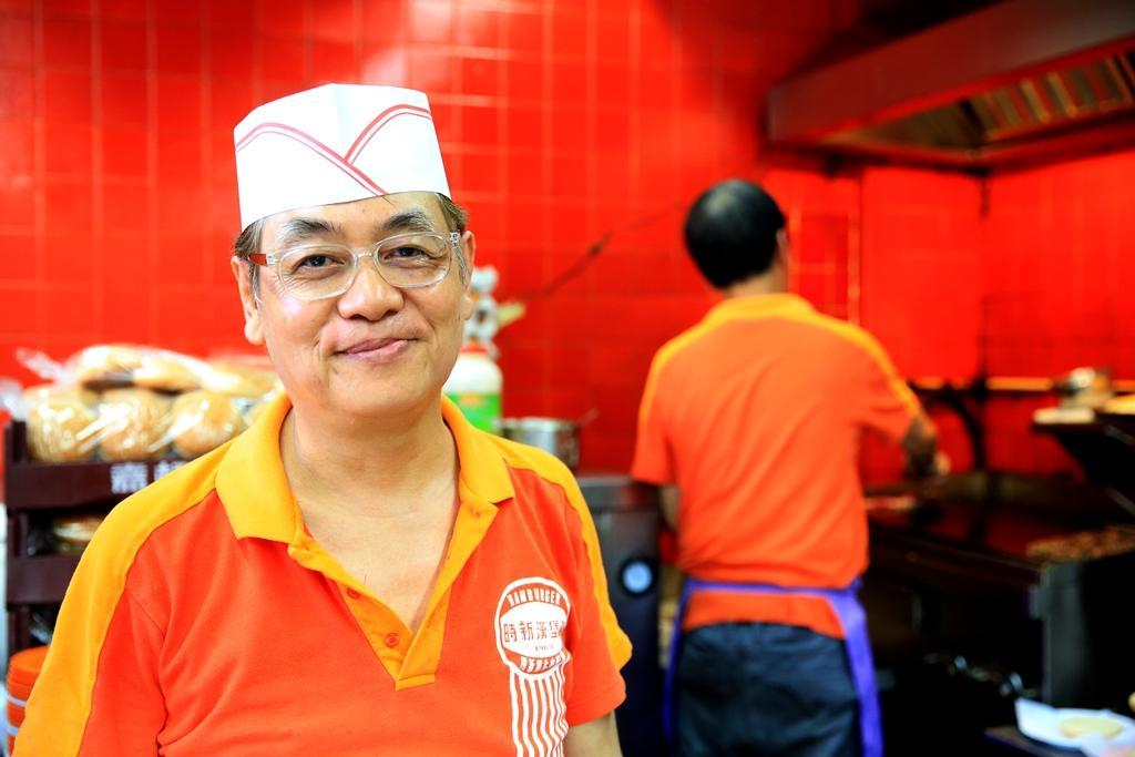 在時新櫃台裡一身橘紅的老闆,笑容可掬。