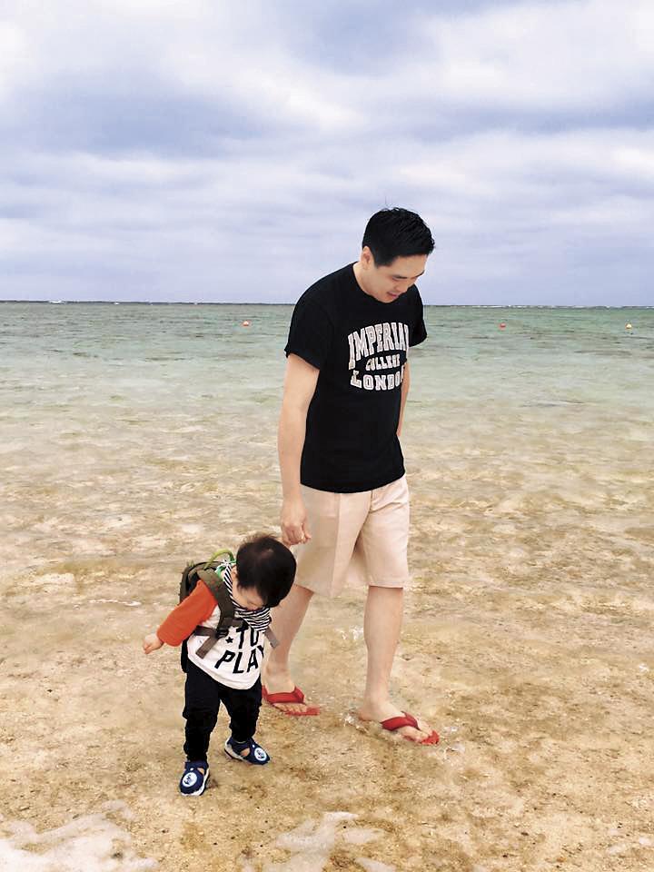 2016年中,麻衣曬出王泉仁牽著小孩在沖繩海灘的照片,父愛滿滿。(翻攝自麻衣臉書)