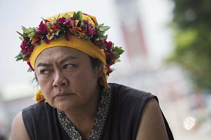 巴奈在總統府前的凱道上接受採訪,她穿著部落傳統服飾,頭戴友人獻上的花環,但烈日下她的神情甚是疲憊。