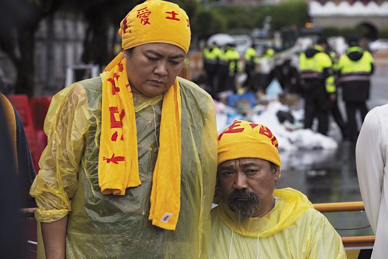 6月2日的清場日,巴奈(左)和伴侶那布(右)始終相依,他們在大雨中神情落寞,身後是被警方拆除後聚集成堆的藝術品和物資。