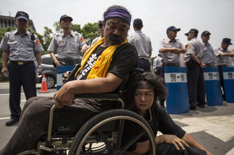 5月2日,警方第一次清場。巴奈(右)與先生那布在凱道被警察團團包圍,神情疲憊落寞。