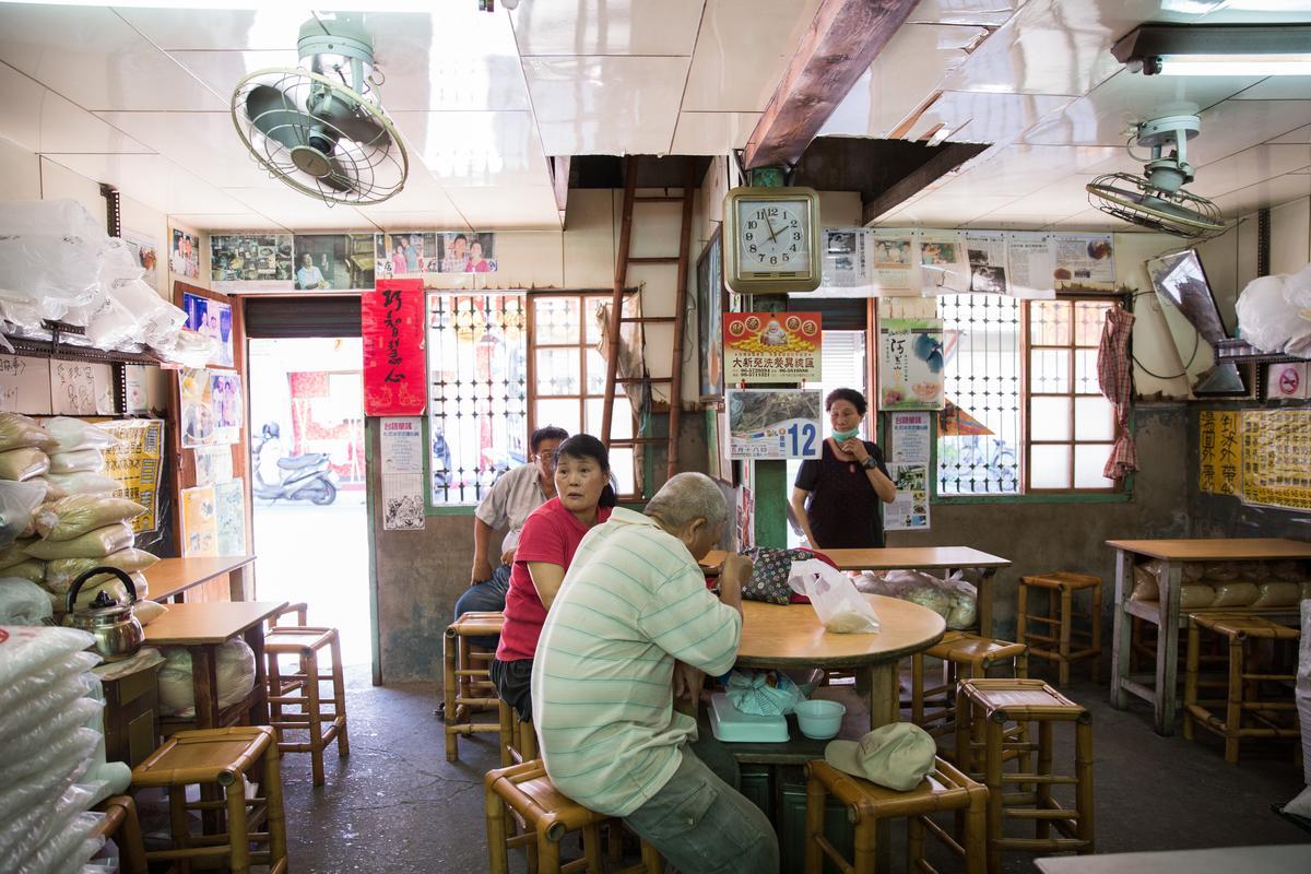 竹凳、木桌、鐵花窗和牆邊成堆的各式糖包,「龍泉冰店」的風景就像台灣老一輩人樸實的生活景況。