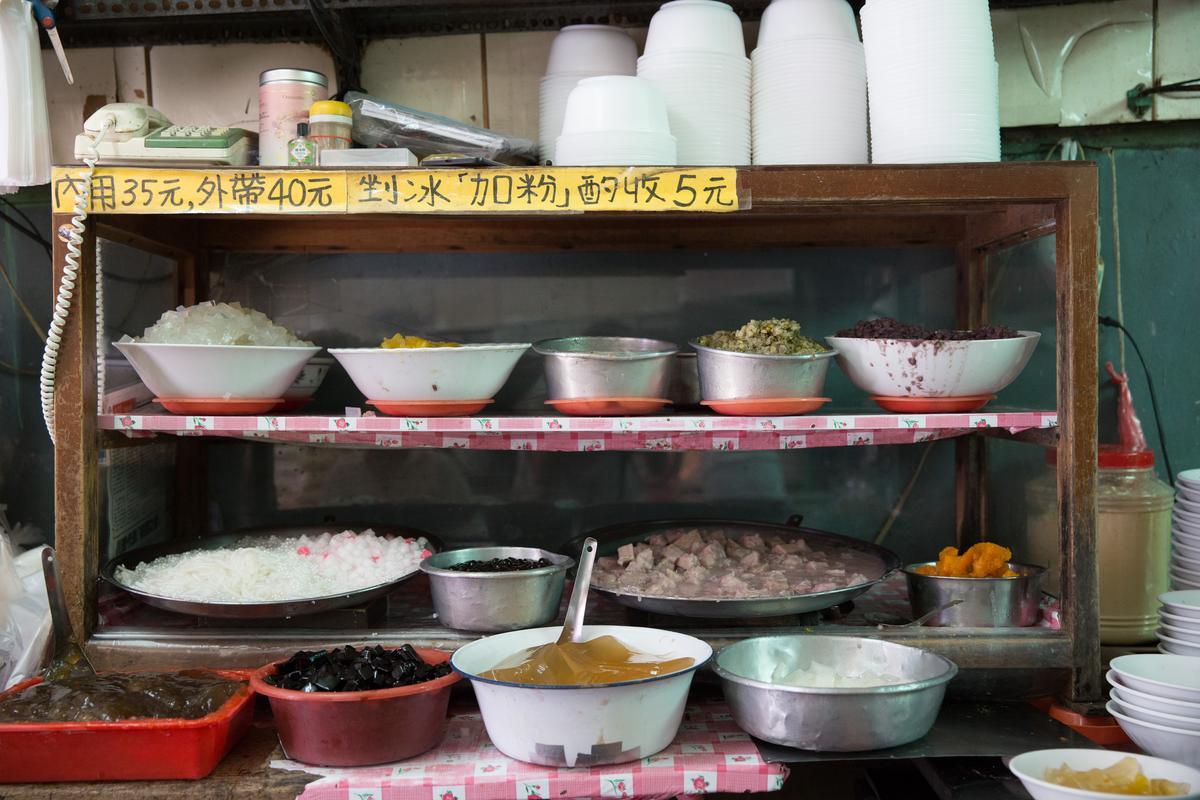 堅持每天手工熬煮的冰料都盛放在這一方小木櫃裡,木櫃每天都得要刷洗,紅色盤子和碗公每天清晨一碗碗擺好,客人點了料,店家就用鐵湯匙一匙匙舀進剉冰裡。