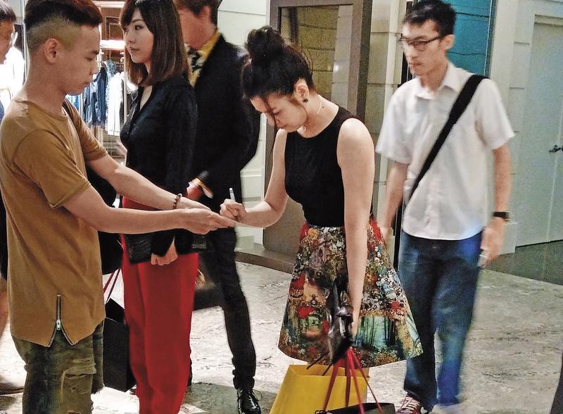 陳妍希一手提著滿滿的袋子,一手幫粉絲簽名,非常親民。