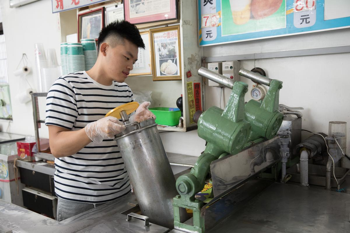 三色冰製作步驟4:把沈重的冰桶搬運到前台冷凝機的齒輪式攪拌區固定。
