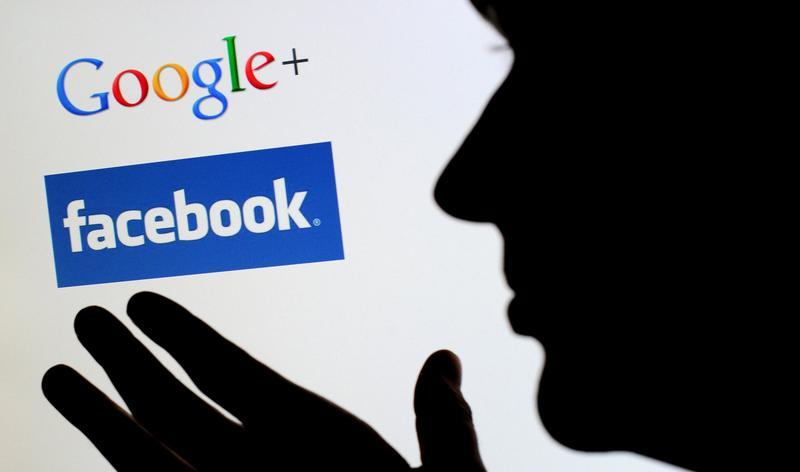 用戶對著電腦螢幕中Google+和Facebook的商標符號。(東方IC)