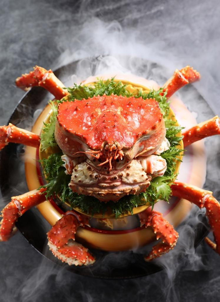 煙霧瀰漫中,「帝王蟹蓋飯」豪華上桌。(時價,約580元/100g,圖中約1,000g、5,800元)