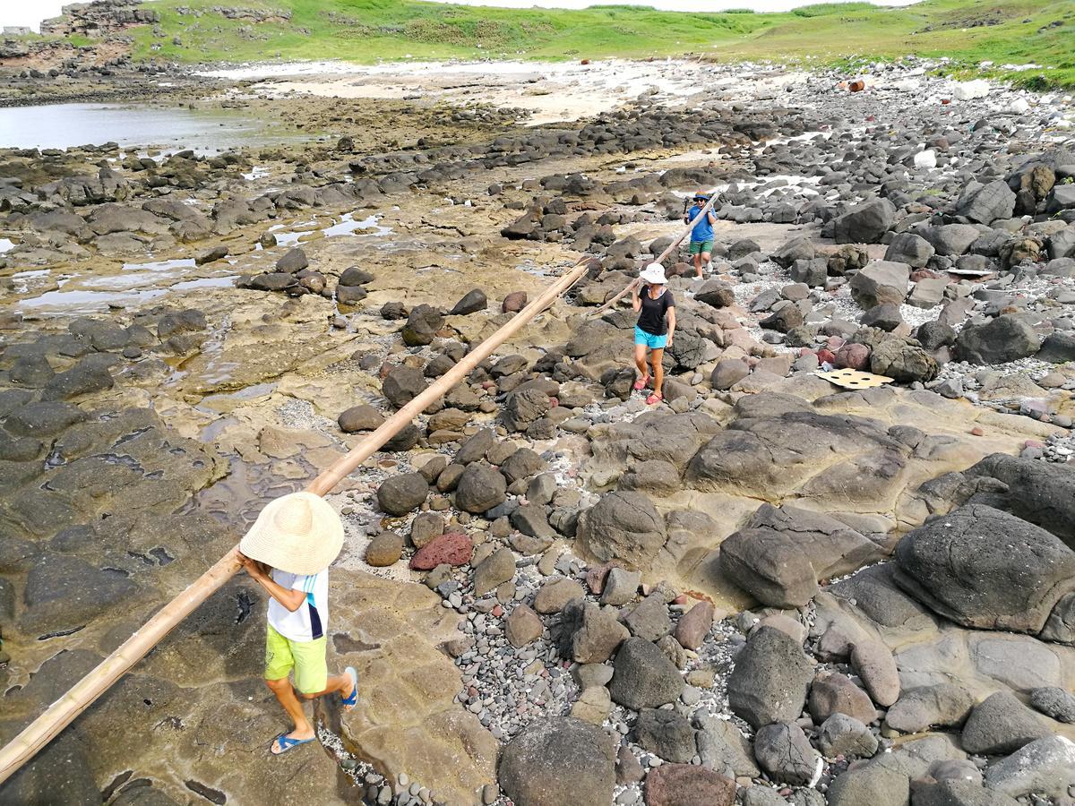 在充滿廢棄物的海灘上,尋找可以搭乘棚子的長竹竿。