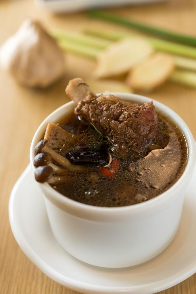 以整顆黑蒜燉煮的「黑蒜肉骨茶」,湯色濃郁帶胡椒辣味。(150元/碗)