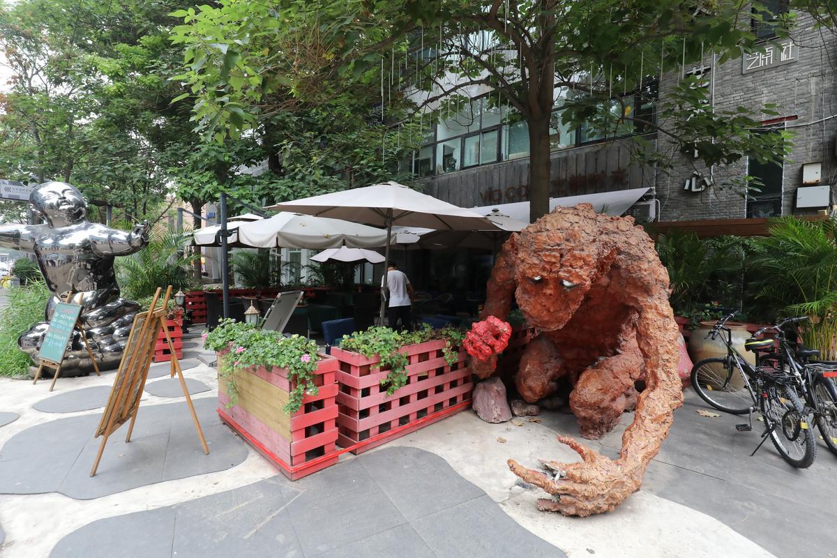 露天咖啡座旁擺著一尊醜怪塑像,是要倒胃口呢?還是倒胃口呢!