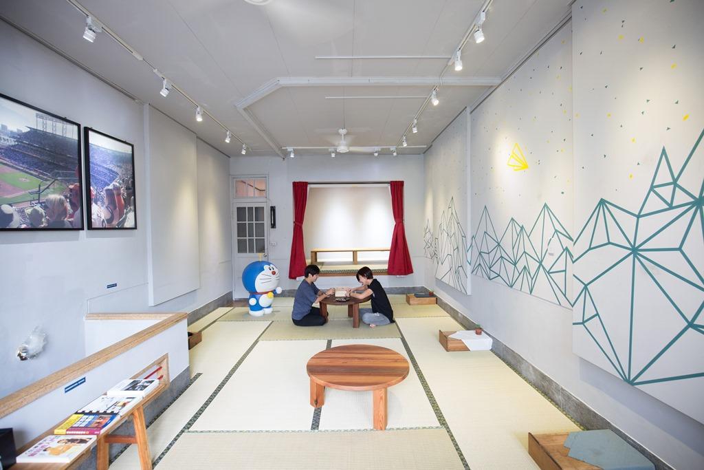二店2樓設計為榻榻米座位、紅色布簾舞台、老闆平收集的小叮噹大型玩具,帶點童趣氛圍。