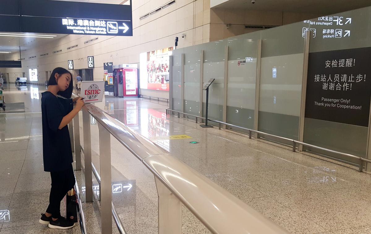 一位手拿「TSMC(台積電)」看板的工作人員,等待著來自台灣的工程師。
