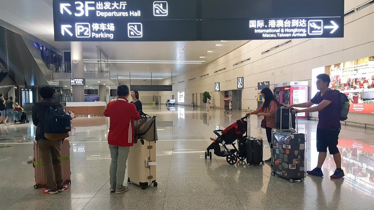 10位穿著輕便的年輕人,一前一後的拉著行李箱走出大廳。