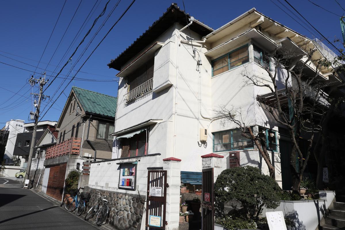 覺王山公寓是一棟老派的兩層樓白色公寓。