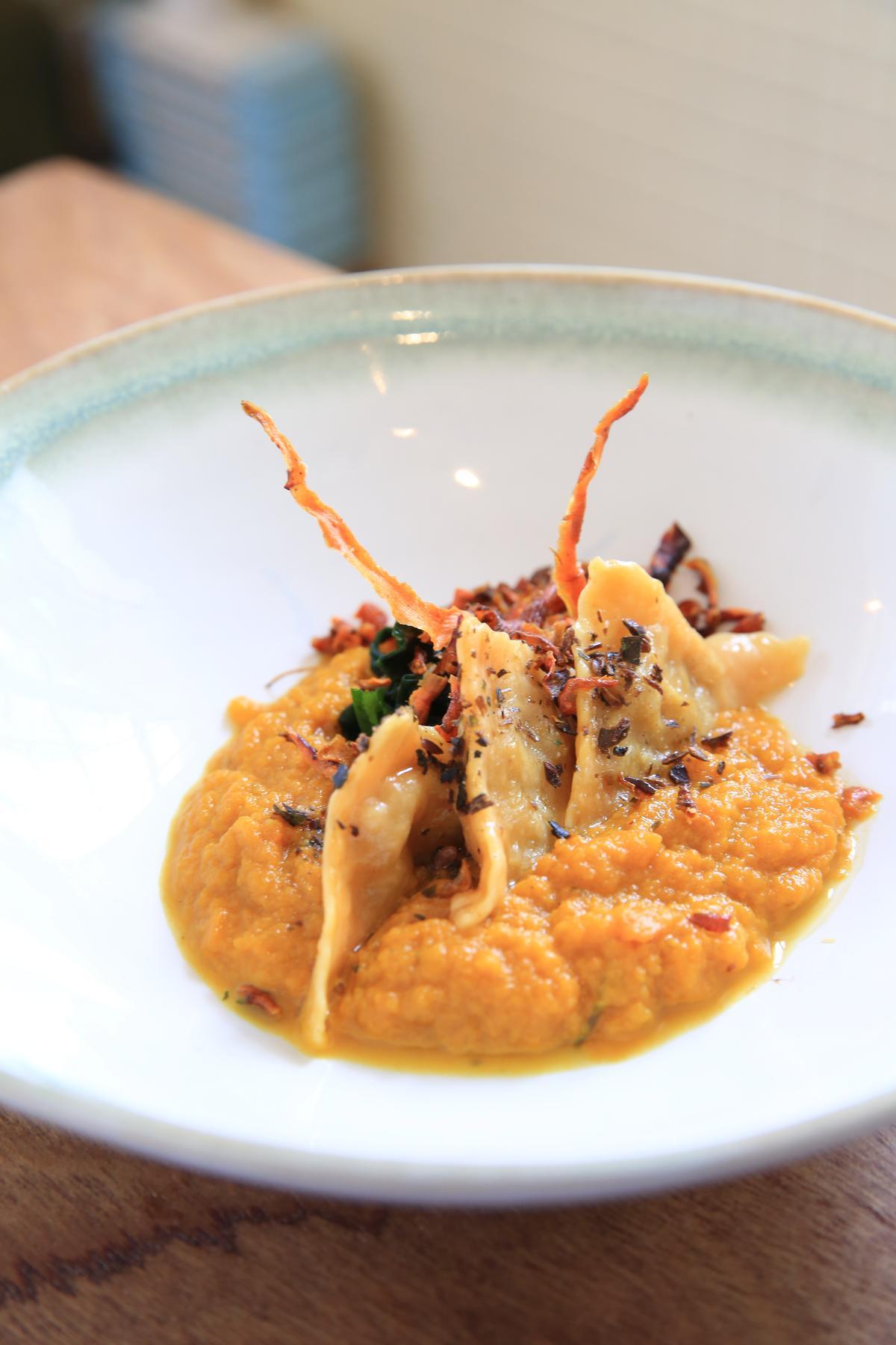 西式手工餃淋上以紅蘿蔔、柳橙、茄子、番茄泥醬,再綴以海帶芽,上頭還插了兩根假裝是培根的紅蘿蔔脆片。