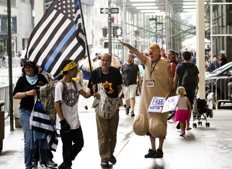 2017年8月15日,紐約川普大樓外帶著川普面具的民眾對著川普的支持者做出充滿嘲諷意味的納粹式敬禮。(東方IC)