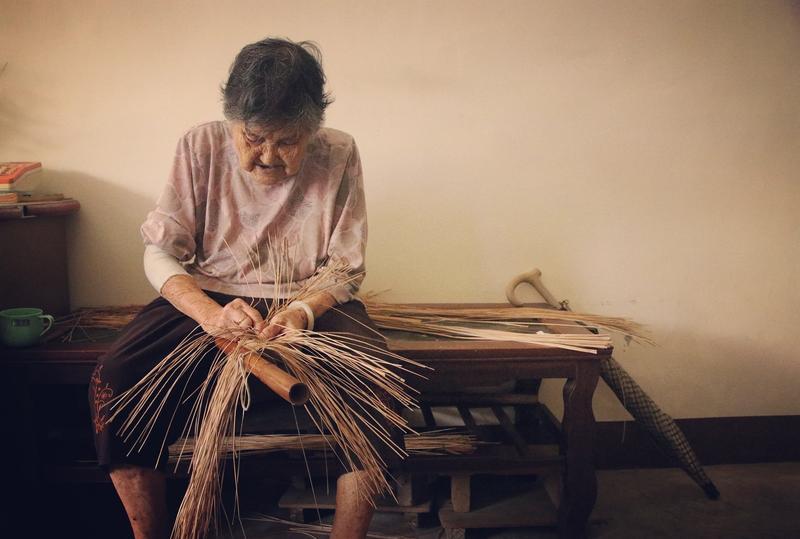 94歲高齡的許陳真阿嬤,至今仍專注地以苑裡藺草編織名片夾。(圖片提供/藺子,攝影/李易紳)