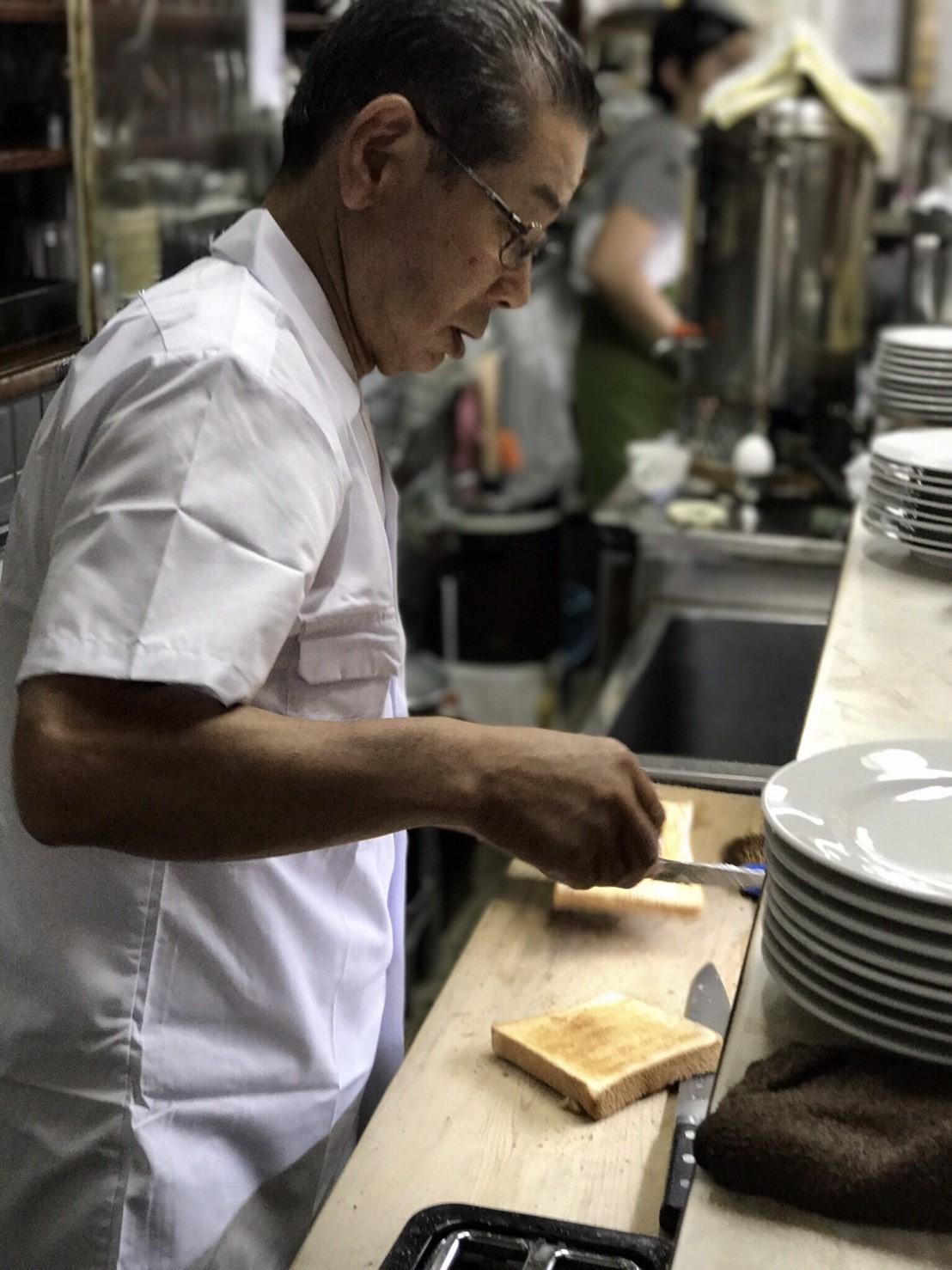 坐在吧檯邊可以看到咖啡師在吐司上抺奶油,還可以聽到快刀切下時傳來「涮涮涮涮」的酥爽聲音。